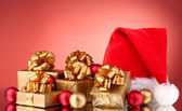 Beautiful Christmas hat, gifts and Christmas balls on red background — Foto Stock