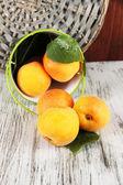 杏子在附近柳条杯垫木桌上的斗 — 图库照片