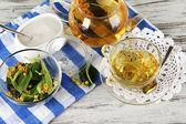 Tetera y taza de té con linden en mesa de madera — Foto de Stock