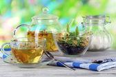 Tetera y taza de té con linden en mesa de madera en el fondo de la naturaleza — Foto de Stock