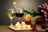 Composición con vino, queso azul y uva de mesa de madera, sobre fondo gris — Foto de Stock