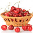 Cherry berries in wicker basket isolated on white — Stock Photo