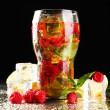 Iced tea with raspberries and mint on dark background with yellow light — Stock Photo