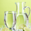Glass pitcher of water and glass on green background — Stock Photo