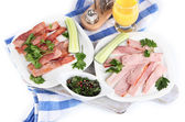 Bacon on plates on napkin on board isolated on white — Stock Photo