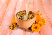 Flores de caléndula sobre fondo de madera y botellas de medicina — Foto de Stock