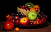 Assortment of juicy fruits on wooden table, on dark background — Stock Photo