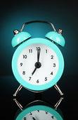 Blue alarm clock on dark blue background — Stock Photo
