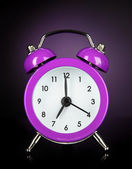 Purple alarm clock on dark purple background — Stock Photo