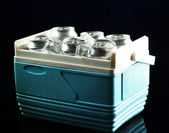 Metal cans of beer with ice cubes in mini refrigerator, on dark blue background — Stock Photo