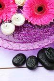 Wellness stones, mooie gerberabloemen en kaarsen op water — Stockfoto
