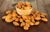 Almond in wooden bowl, on wooden background — Stock Photo