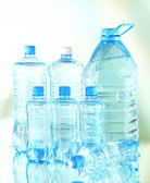 Water in different bottles on light background — Stock Photo