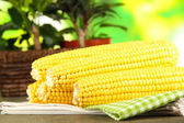 Crude corns on napkin on wooden table on nature background — Stock Photo