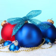 Beautiful blue and red Christmas balls and cones on snow on blue background — Stok fotoğraf