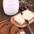 Butter on wooden holder surrounded by bread and milk on wooden table close-up — Stock Photo
