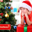 Child in Santa hat near Christmas tree with big gift — Stock Photo #29250445
