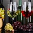 Photo: Assortment of wine in glasses and bottles on grey background