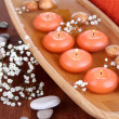 Beautiful candles in water on wooden table close-up — Stock Photo