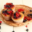 Tasty muffins with berries on white wooden table — Stock Photo #29251121