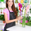 Beautiful girl florist with flowers in flowers shop — Stock Photo #29251899
