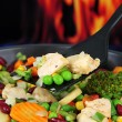 Casserole with vegetables and meat on pan, on fire background — Stock Photo #29251941