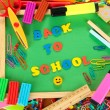 Foto de Stock  : Small chalkboard with school supplies on wooden background. Back to School