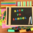 Foto Stock: Small chalkboard with school supplies on wooden background. Back to School