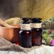 Medicine bottles and mortar with thistle flowers — Stock Photo #29253381