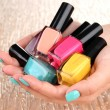 Beautiful woman hands with blue manicure and several bottles with nail polish, on color background — Stock Photo #29253537