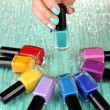 Beautiful woman hands with blue manicure and several bottles with nail polish, on color background — Stock Photo #29253543