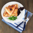Pizzcalzone on plate on napkin on wooden table — Stock Photo #29253561