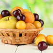 Bright summer fruits in basket on wooden table on natural background — Stockfoto