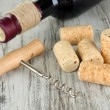 Corkscrew with wine corks and bottle of wine on wooden table close-up — Stock Photo #29253955