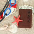 Stock Photo: Composition with lifebuoy, goggles, notepad and money, on sand background