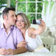 Young couple  taking  photo with  mobile phone in restaurant — Stockfoto