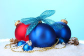 Beautiful blue and red Christmas balls and cones on snow on blue background — Stockfoto