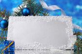 Leere postkarte, weihnachtskugel und tanne auf blauem hintergrund — Stockfoto