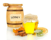 Jar of honey, wooden barrel, drizzler and dried fruits isolated on white — Stock Photo