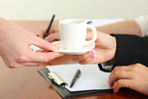 Close up of businesswoman hands with cup of coffee during teamwork — Stock Photo
