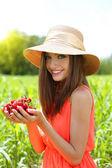 Retrato de mujer joven hermosa con las bayas en el campo — Foto de Stock