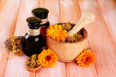 Medicine bottles and calendula flowers on wooden background — Stock Photo