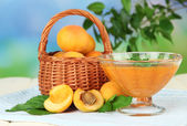 Apricot jam in glass bowl and fresh apricots, on wooden table, on bright background — Stock Photo