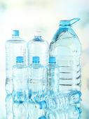 Acqua in bottiglie diverse su sfondo chiaro — Foto Stock