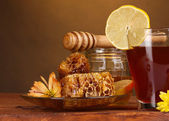 Honey, lemon, honeycomb and a cup of tea on wooden table on brown background — Stock Photo