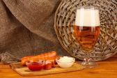 Cerveza y salchichas a la plancha sobre una mesa de madera sobre fondo de tela de saco — Foto de Stock