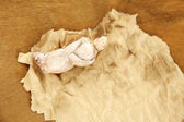 Old paper with figurine, on wooden background — Stock Photo