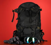 Winter sport glasses, helmet and gloves, backpack, on red background — Photo