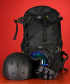 Winter sport glasses, helmet and gloves, backpack, on red background — Stockfoto