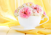 Roses in cup on wooden table on yellow cloth background — Stock Photo